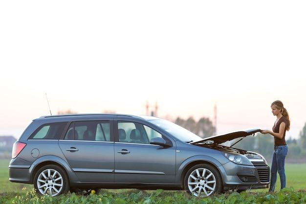 Молодая женщина и автомобиль с откинутым капотом