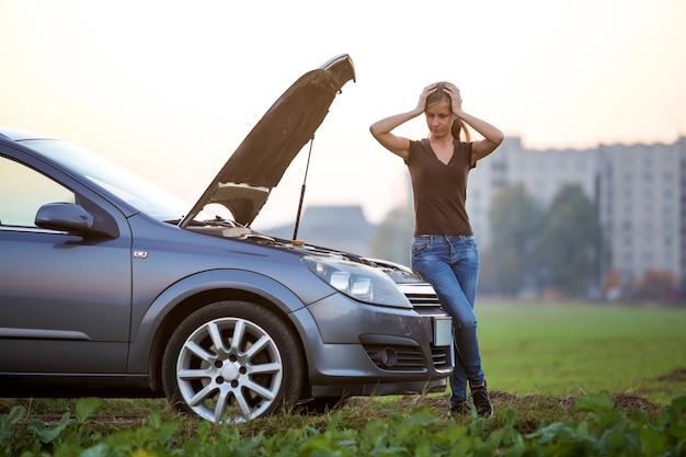 Молодая женщина и машина с раскрытым капотом.