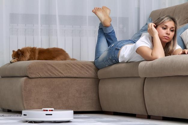 ロボット掃除機が掃除されている間、若い女性と犬がソファでリラックス