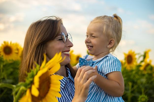 ひまわり畑で若い女性と彼女の腕の中で小さな女の子。子供とお母さん。