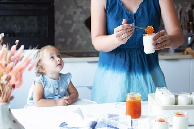 若い女性と赤ん坊の娘がキッチンで自家製ヨーグルトを準備しています。有機エコ天然乳製品