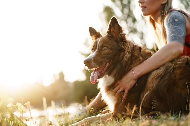Молодая женщина и собака бордер-колли проводят время в парке