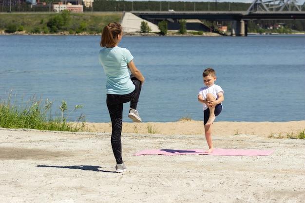Молодая женщина и ребенок растягиваются и делают разминку у озера