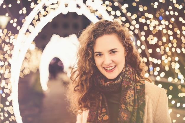 Молодая женщина и рождественские огни и украшения рождество и новый год концепция