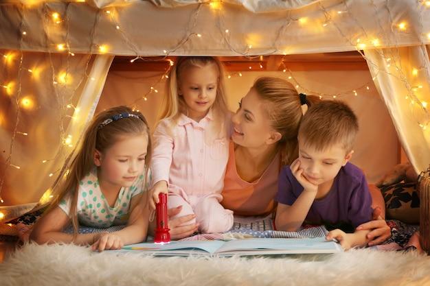 Молодая женщина и милые дети читают книгу в лачуге дома