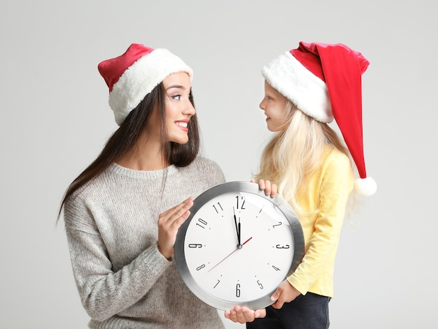 밝은 표면에 시계와 산타 모자에 젊은 여자와 귀여운 소녀