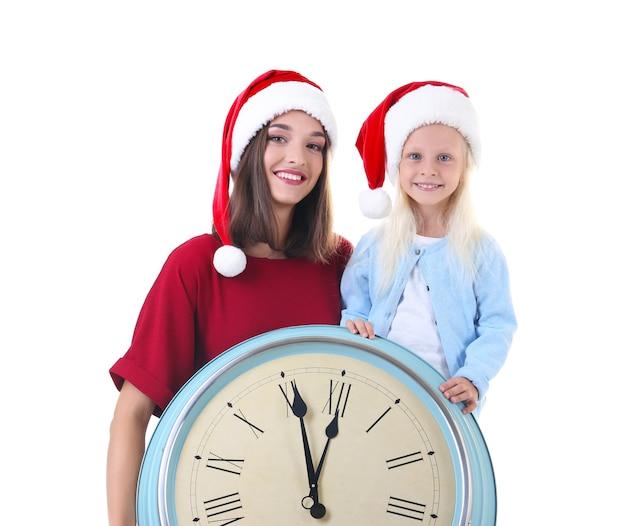 젊은 여자와 흰 벽에 시계와 산타 모자에 귀여운 소녀.