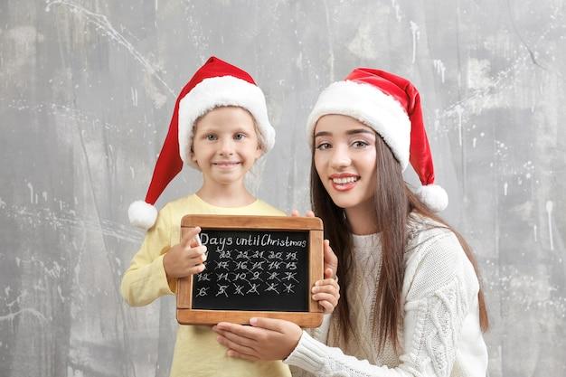 Молодая женщина и милая маленькая девочка в шляпах санта-клауса с классной доской, считая дни до рождества