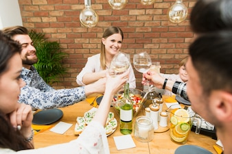 Young woman and friends clinking wine glasses