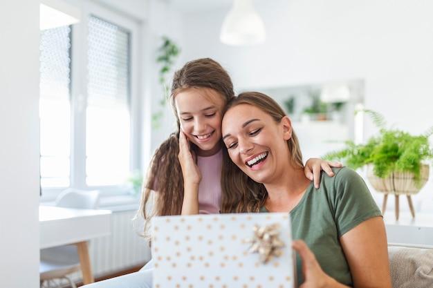 Молодая женщина и девушка дома празднуют день матери, сидя на диване, дочь обнимает мать, целует щеку, мама смеется радостно, держа подарочную коробку