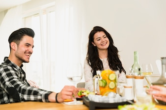 Young woman and handsome man sitting at table