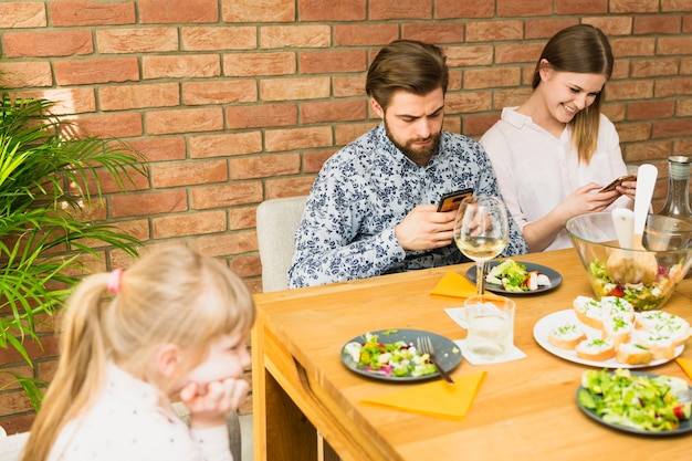 テーブルに座っている若い女性とハンサムな男