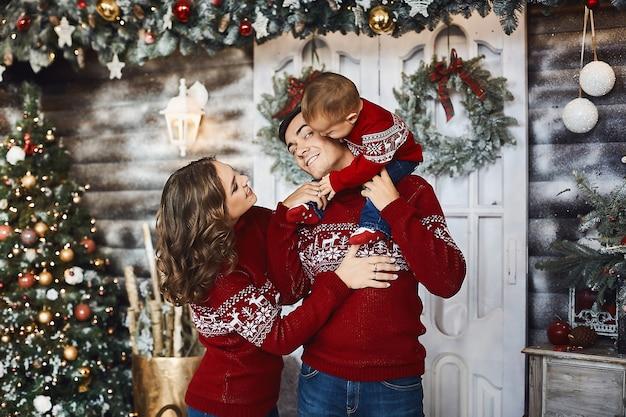 クリスマスのインテリアでポーズをとって彼の肩に小さな男の子を持つ若い女性とハンサムな男。