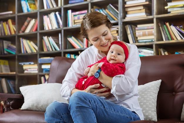 若い女性と自宅の図書館のソファで彼女の赤ん坊の娘
