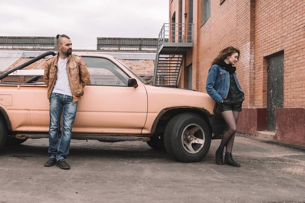 Молодая женщина и ее парень стоя возле машины