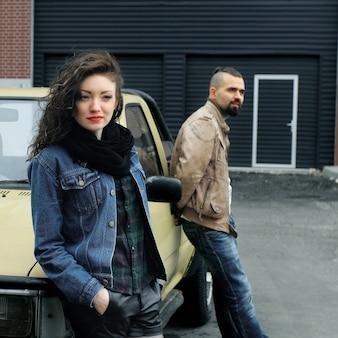 젊은 여자와 그녀의 남자 친구가 차 근처에 서
