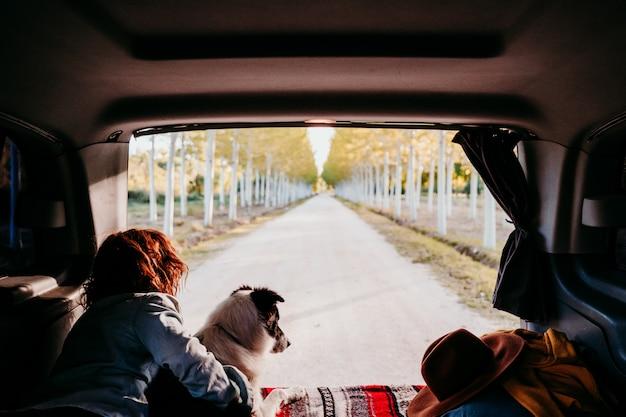 若い女性と彼女のかわいいボーダーコリー犬がバンでリラックス。旅行の概念。