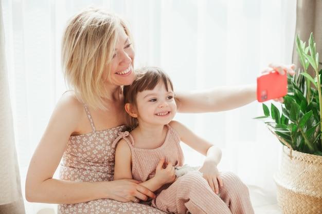 Молодая женщина и ее милая маленькая дочь сидят вместе и обнимаются, делают селфи на смартфоне и улыбаются