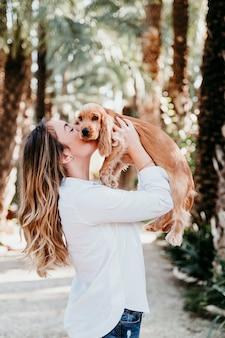 若い女性と公園で屋外のコッカースパニエルの彼女のかわいい子犬