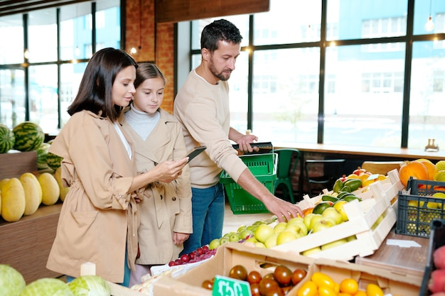 Молодая женщина и ее дочь просматривают список покупок в блокноте, пока мужчина с корзиной выбирает фрукты