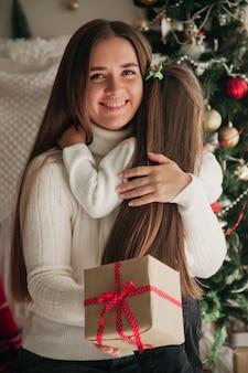 젊은 여자와 그녀의 딸 크리스마스 트리 앞에 앉아 선물을 들고