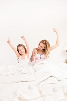 Молодая женщина и ее дочь просыпаются и протягивают руки утром