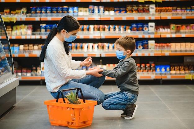 젊은 여자와 보호 얼굴 마스크를 착용하는 그녀의 아이는 슈퍼마켓에서 음식을 쇼핑