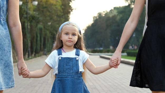サマーパークで手をつないで一緒に歩いている長い髪の若い女性と彼女の小さな娘。