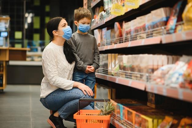 젊은 여자와 그녀의 작은 아들 입고 보호 얼굴 마스크는 슈퍼마켓에서 음식을 쇼핑
