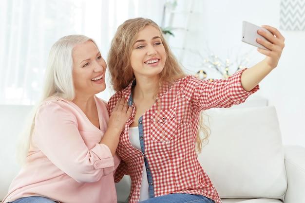 家で自分撮りをしている若い女性と彼女の母親