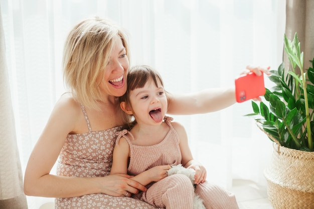 Молодая женщина и ее хорошенькая маленькая дочь сидят вместе и дурачатся, делая селфи на смартфон