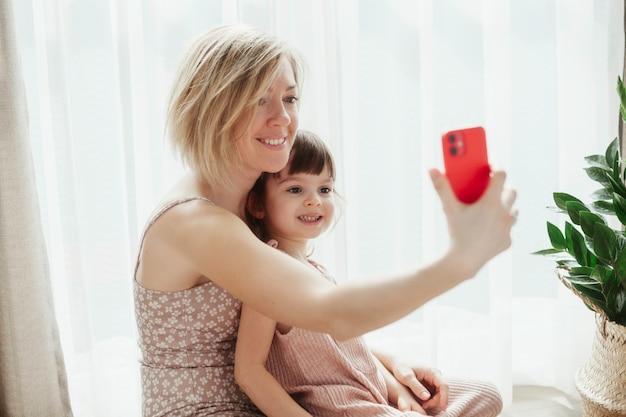 Молодая женщина и ее хорошенькая маленькая дочь сидят вместе и обнимаются, делая селфи на смартфоне