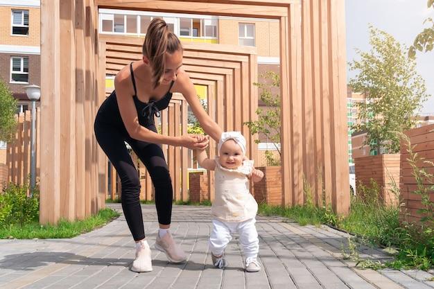 若い女性と彼女の幼児の娘が街の中庭を歩く子供は歩くことを学ぶ