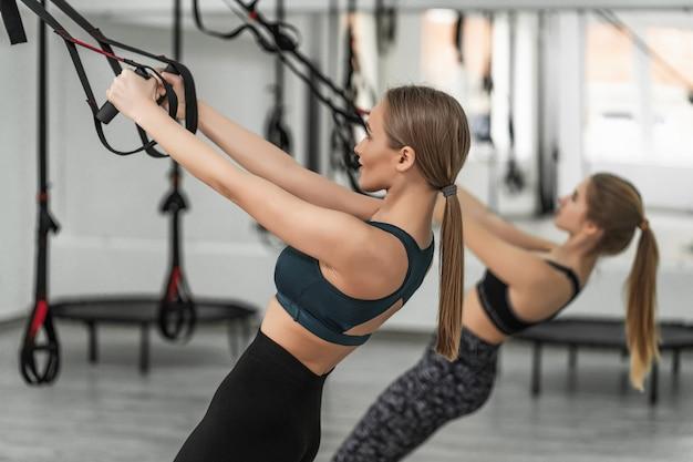 젊은 여성과 그녀의 트레이너 훈련 운동은 체육관에서 trx 피트니스 스트랩으로 팔 굽혀 펴기