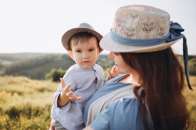Молодая женщина и маленький мальчик в поле, на открытом воздухе. мать держит ее сына, улыбаясь, как носить винтажную одежду и соломенные шляпы.