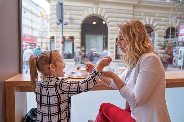 若い女性と小さな女の子がカフェでケーキを食べる