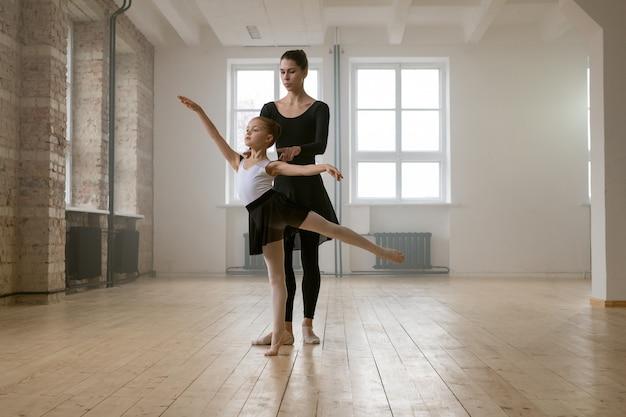 Молодая женщина и маленькая девочка, стоящие вместе в одной балетной позе и танцующие в танцевальной студии