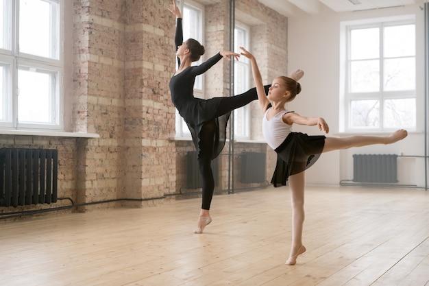 若い女性と少女が同じバレエポーズで一緒に立って、ダンススタジオで踊る