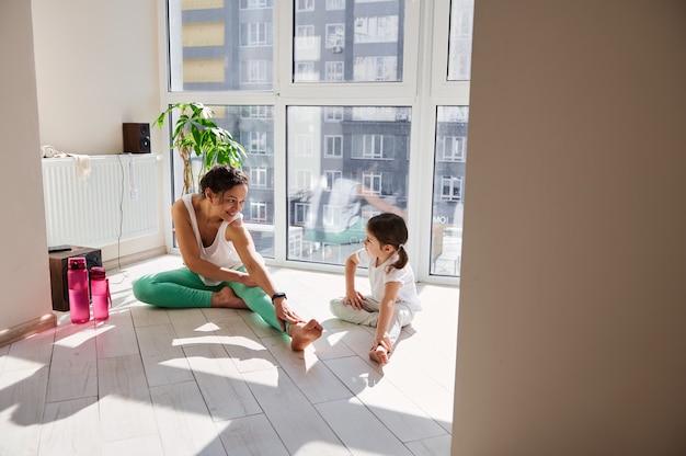 Молодая женщина и маленькая девочка, протягивая тело во время тренировки в помещении. мать и дочь занимаются йогой дома.