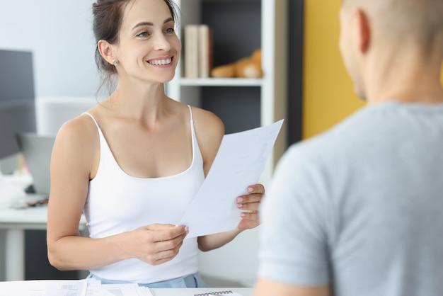 若い女性と男性は自宅で手に書類を持ってテーブルに座っています