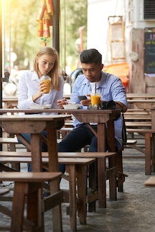 若い女性と男性が屋外カフェでさわやかなカクテルを飲む