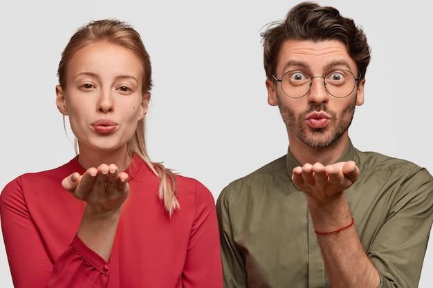 Молодая женщина и мужчина складывают губы, держат ладони возле ртов, дуют воздушный поцелуй, имеют романтический вид, выражение любви, носят модную одежду, изолированные на белой стене. сладкий воздушный поцелуй