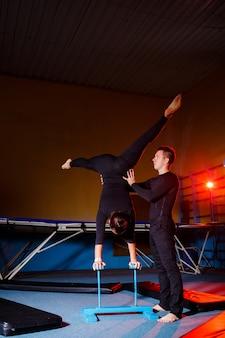 Гимнасты молодые женщины и мужчины делают акробатические упражнения в тренажерном зале. занятия спортом, здоровый образ жизни
