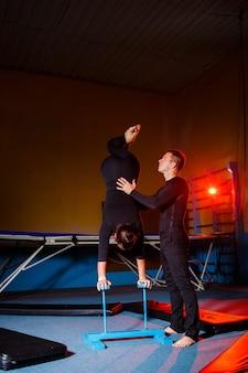 젊은 여자와 남자 체조 선수는 체육관에서 곡예 운동을 합니다. 스포츠 활동, 건강한 생활 방식