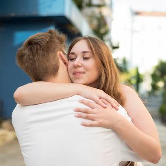 Молодая женщина и мужчина обнимаются после окончания карантина