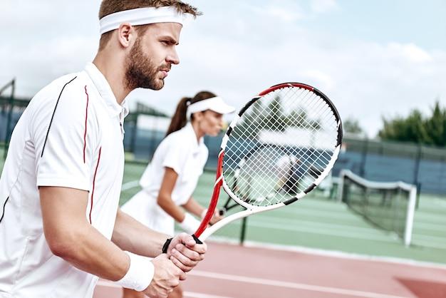 白いスポーツウェアの若い女性と男性は、ゲームに完全に集中している手にラケットを持ってコートに立っています