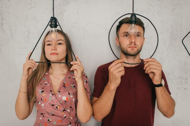 若い女と男は、三角形と円のランプを通して見えます。