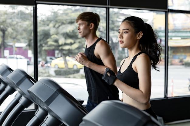 젊은 여성과 남성이 체육관에서 현대적인 전기 러닝머신에서 나란히 달리고 있습니다. 배경에 맞는 젊은 남자와 디딜 방아에서 실행 하는 예쁜 아시아 여자. 전기 디딜 방아에 젊은 부부. 프리미엄 사진