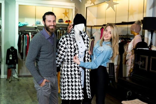 Молодая женщина и мужчина покупают теплые куртки в магазине одежды.