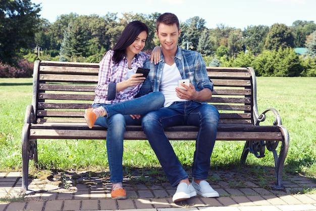 젊은 여자와 남자는 공원 벤치에 앉아 스마트 폰을 찾고